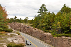 Car on a road through a rock cut Stock Images