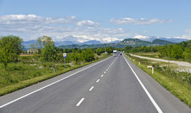 Car road with snow covered mountains in the back Stock Image