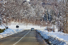 Car on the road among snowy fields. Royalty Free Stock Photo