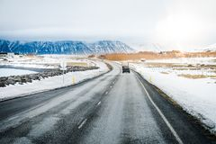 Car on the road or street or road trip surrounding by snow with. Snow-capped mountain background in Iceland. Beautiful natural view and winter Landscape picture stock photos