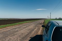 The car is on the road. Summer road on which there is a parked car. Travelling by car stock photo