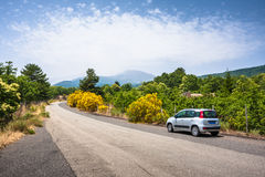 Car on the road to Etna, with volcano in background, Sicily Stock Image