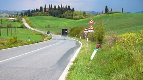 Car on a road through the tuscanian hills stock video footage