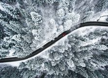 Car on road in winter trough a forest covered with snow. Aerial photography of a road in wintertime trough a forest covered in snow. High mountain pass in the royalty free stock images