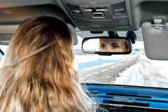 In the car on the winter road you can see the eyes in the rear-view mirror of the blonde girl sitting behind the wheel royalty free stock photos
