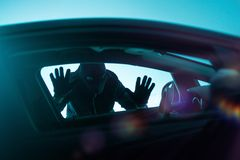 Car Robbery Concept. Car Robber Concept Photo. Robber Looking Thru Car Window. Carjacking Theme Stock Images