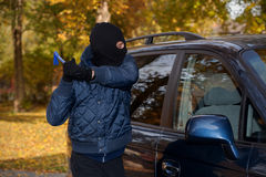 Car robbery. A masked man robbing a car by breaking the window Royalty Free Stock Photo