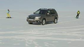 Car rolls skiers on ice of Lake Baikal. stock video footage