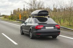 Car with roof luggage box container for travel on a road Royalty Free Stock Photo