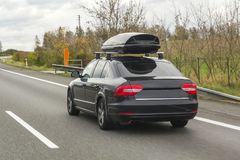 Car with roof luggage box container for travel on a road.  Royalty Free Stock Photos
