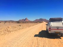 Car with roof tent on desert road stock photo