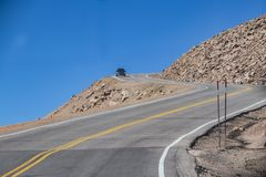 Car rounding sharp bend with steep dropoff on dangerous mountain road with blue sky behind.  stock photos