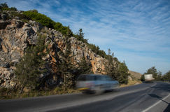 Car running  fast on a curved  dangerous  mountain road Stock Images