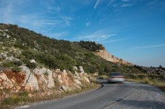 Car running  fast on a curved  dangerous  mountain road Stock Photos
