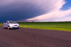Car running storm clouds