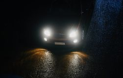 A car is running on a wet road at night unique photo. A modern car is running on the wet road at night with headlights on isolated unique photograph Stock Image