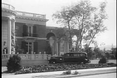 Car rushing past people in front of building entrance, 1930s stock footage