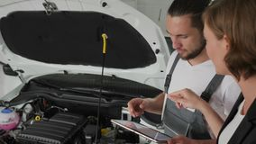 Car`s master shows technical condition Car on tablet, Auto repairman Shows on breakdown vehicle, auto mechanic advises stock video