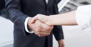 Car sale. Customer and salesman shaking hands. Car sale. Female customer and salesman shaking hands at dealership royalty free stock photography