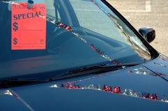 Car For Sale on Lot. A car on a car lot for sale with tag in the window an streamers reflecting on the hood stock photo