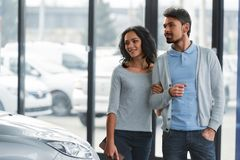 Car sales. Beautiful young couple in the showroom, choosing a car royalty free stock photos