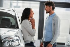 Car sales. Beautiful young couple in the showroom, choosing a car stock image