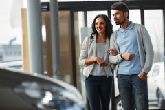 Car sales. Beautiful young couple in the showroom, choosing a car royalty free stock image