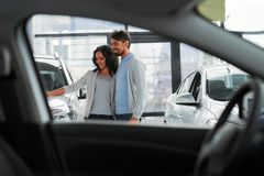 Car sales. Beautiful young couple in the showroom, choosing a car stock photo