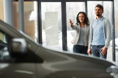 Car sales. Beautiful young couple in the showroom, choosing a car royalty free stock images