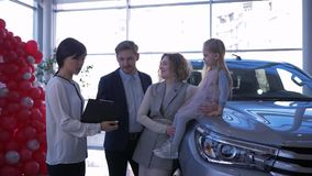 Car sales center, consumer couple with child advise with worker auto shop about buying family vehicle at showroom. Car sales center, consumer couple with child stock video footage