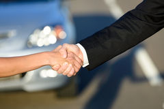 Car sales concept. Man and woman closing a car sale agreement with a handshake. Salesman and buyer shaking hands Royalty Free Stock Photography