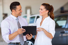 Car sales consultants. Two happy car sales consultants working inside vehicle showroom Stock Photography