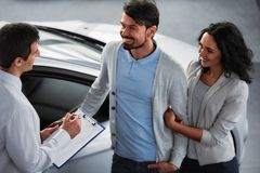 Car sales. Handsome young car salesman isnstanding at the dealership telling about the features of the car to the couple royalty free stock photography