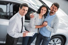 Car sales. Handsome young car salesman isnstanding at the dealership telling about the features of the car to the couple stock photos