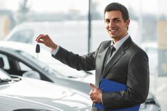 Car sales. Handsome young car salesman is standing at the dealership holding a keys stock photo