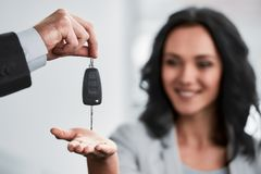 Car sales. Happy women receives the keys to a new car from a sales manager royalty free stock photo