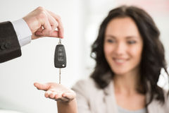 Car sales. Happy woman receives the keys to a new car from a sales manager royalty free stock photo