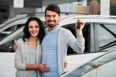 Car sales. Happy young couple with keys from a new car after automobile purchase in dealer showroom stock photography