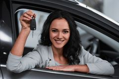 Car sales. Happy young woman is holding keys to new car and looking at the camera stock images