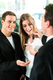 Car sales - key being given to couple. Sales situation in a car dealership, the dealer is handing auto keys to a young couple, they are excited, cars standing in Royalty Free Stock Photo