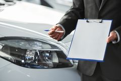 Car sales. Man is holding a contract in a dealership. Close-up royalty free stock photo