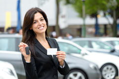 Car sales and rental. Successful female luxury car sales representative showing car key and business card  in automobile trade fair. Beautiful brunette Royalty Free Stock Photos