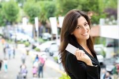 Car sales representative. Successful female car sales representative showing business card  in automobile trade fair. Beautiful brunette saleswoman outdoor Royalty Free Stock Photography