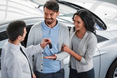 Car sales. Man is giving the key of the new car to the young attractive owners stock images