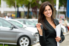 Car sales woman. Female car seller holding car keys. Caucasian saleswoman in luxury vehicle trade fair. Auto rental or sales concept Stock Image