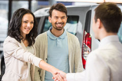 Car sales. Young couple grateful sales manager for advice in auto salon Stock Photos