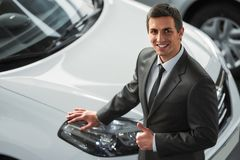Car sales. Young man consultant in showroom is standing near car. Top view stock image