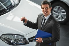 Car sales. Young man consultant in showroom is standing near car. Top view stock images