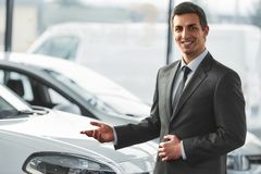 Car sales. Young man consultant in showroom is standing near car. Top view royalty free stock photos