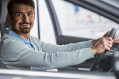 Car sales. Young man is sitting in the car in the showroom stock images